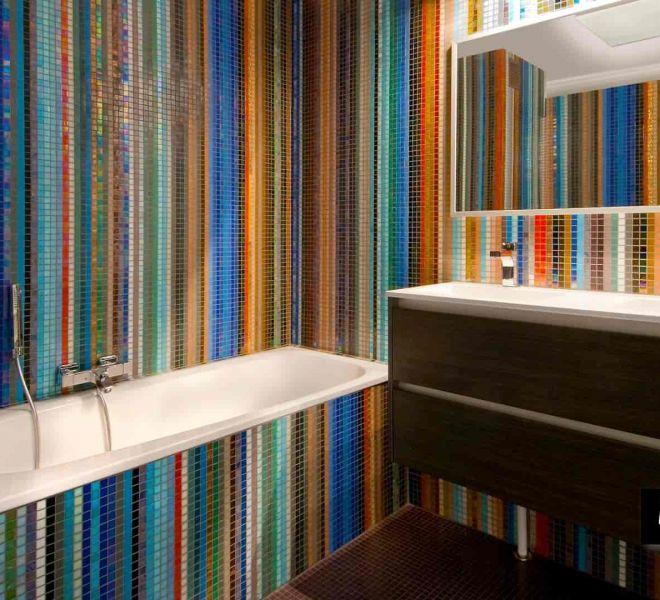Een badkamer van glasmozaïek in alle kleuren van de regenboog. Keuzes waren door de eigenaresse (kunstenares) moeilijk te maken. Waarom zou je ook kiezen?
