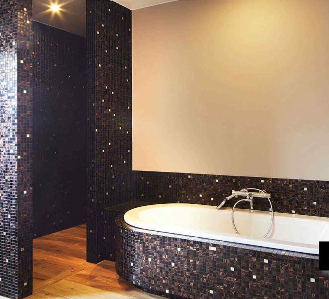 Badkamer met glasmozaïek in de kleuren bruin/zwart. Gecombineerd met 24 karaats goud. Tijdloos en elegant. Rondingen zijn uitstekend te betegelen met mozaïek.