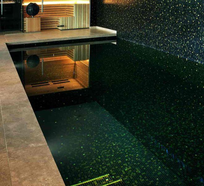 Milovito dé specialist in glasmozaïek maatwerk. Hier werd gekozen voor een zwarte mix met verloop van gouden tegeltjes in het zwembad, douche en stoomcabine.