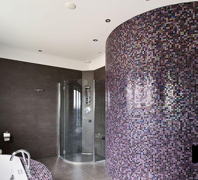 Chique badkamer betegeld met glasmozaïek tegels in de kleuren paars aubergine en zwart parelmoer. Rondingen kan men uitstekend betegelen met mozaïek.